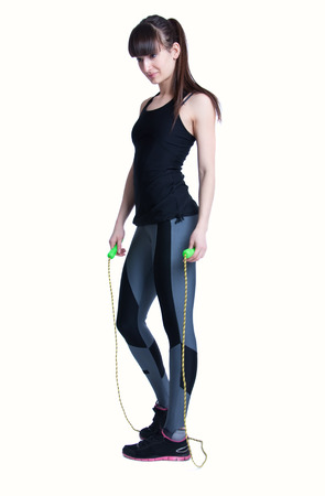 Full length studio portait of pretty young slim and fit brunette woman preparing for workout with a skipping rope, training her muscles to become strong. Isolated on white background photo