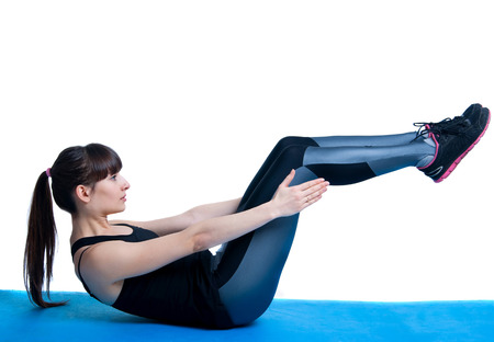 knees bent: Beautiful sporty brunette woman model wearing sportswear tights and top, lying on a blue mat, doing crunches and situps, knees bent. Isolated on white background, copy space Stock Photo