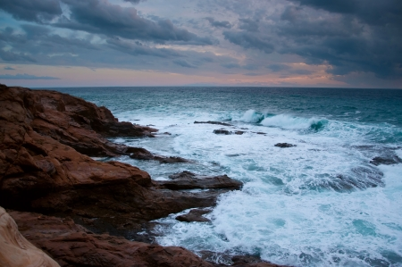 Stormy blue Ligurian sea with white spumy waves crashing against brown rocks. During sunset in autumn photo