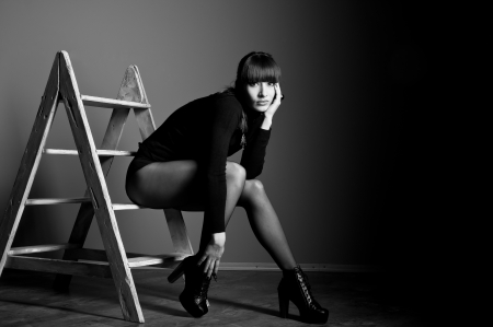 Black white studio portrait of confident beautiful slim woman model with awesome long legs wearing black body suit, boots with high heels, sitting on steps of staircase, looking at camera. Copy space photo