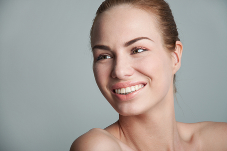 Studio closeup portrait of young pretty woman model wearing tender natural makeup, hair pulled back, looking at something aside and smiling with toothy smile. Over gray background, copy space