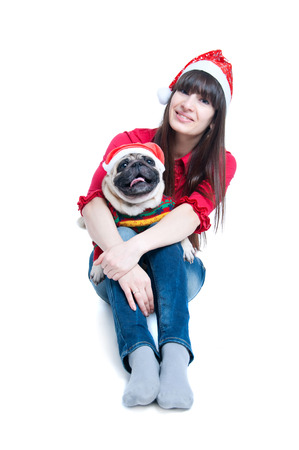 Funny and cute friends a pretty girl and her pug dog pet wearing red Santa Claus caps, having fun, smiling with toothy smiles, dog showing tongue, looking at camera. Isolated on white background Stock Photo