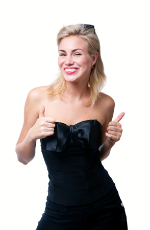 Funny young positive woman model in stylish black top with big silk bow, sun glasses on forehead, bright pink lipstick, having fun, laughing, showing thumbs up, smiling, looking with toothy smile at camera. Isolated on white photo