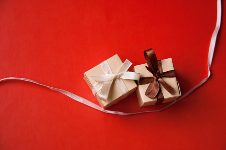 Two wrapped gift boxes with colorful beige and brown satin ribbons and bows on red background in studio. Selective focus, main focus on a beige bow photo