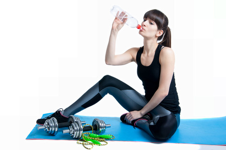 Pretty sporty young slim fit brunette woman sitting on a yoga mat, resting after workout with a skipping rope and dumbbells, drinking water from a bottle, relaxing. In studio isolated on white background photo