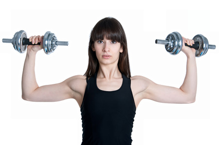 Front view of pretty young slim and fit brunette woman trainer doing workout with heavy metal dumbbells, training her muscles to become strong. In studio isolate on white background photo