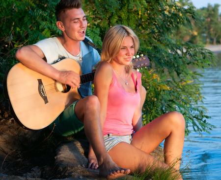 Young pretty couple of man and woman in love sitting on the beach close to each other, man playing the guitar, both smiling, feeling happy together, a man singing to a woman. During sunset photo