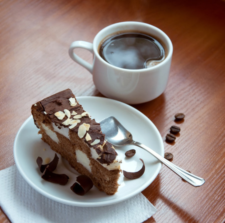 Still life of a cup of strong espresso coffee with a slice of tasty chocolate cake on a saucer with a chess decoration when cut, covered with almond chips on top. On a wooden table. Copy space photo