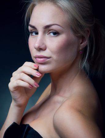 Studio portrait of pretty young blonde woman model with natural makeup, tender pink lip gloss, manicure with nice nail polish, bare shoulders, wearing black top, looking at camera. Over black background photo