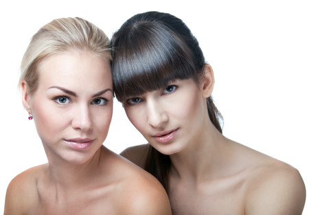 Studio closeup portrait of two young beautiful women models isolated on white background. Selective focus, main focus on the blond woman Stock Photo - 26093939