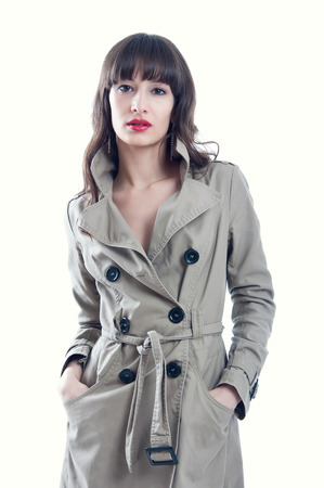 Beautiful young brunette woman model with long hair in lock and straight fringe wearing red lipstick and a rain coat, looking at camera. Isolated on white background photo