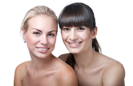 Closeup studio portrait of two young beautiful funny and cute girls having fun, laughing, smiling with toothy smile in front of a camera. Looking at camera. Isolated on white background. Main focus on the brunette