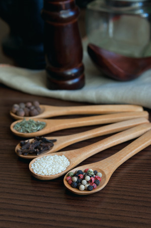 Wooden spoons on a table with a selection of different spices in them like allspices, sesame, red, white and black peppers, dried rosemary, cloves, a linen napkin, a pepper mill, a wooden spoon and other kitchenware on the background. photo