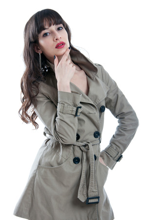 Beautiful young brunette woman model with long hair in lock and straight fringe wearing red lipstick and a rain coat, looking at camera. Isolated on white background Stock Photo