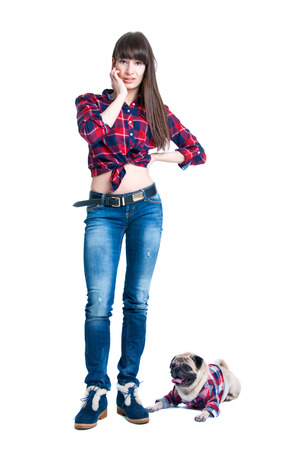 Pretty young brunette woman model with long straight hair standing together with her friend pug dog pet, both wearing checked pattern shirts girl wearing jeans and cool winter shoes. Isolated on white photo