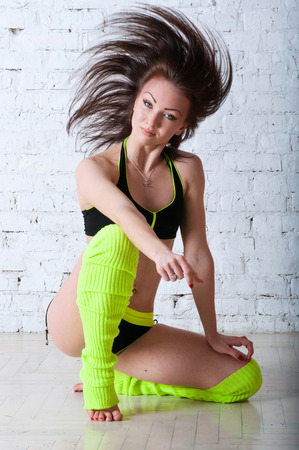 Pretty sporty barefooted woman dancer wearing black yellow concert costume, dancing and posing in studio, hair flying high. On the floor against a brick wall photo