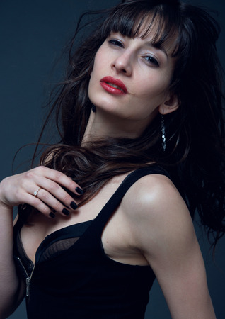 Studio portrait of young sexy brunette woman model wearing tight black dress, stripped bra, red lipstick, looking at camera, wind blowing and disheveling her long curly hair. Copy space photo