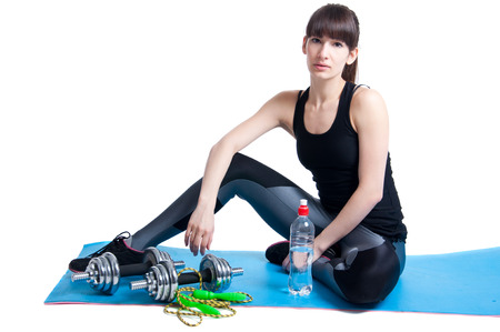 Pretty sporty young slim fit brunette woman sitting on a yoga mat, resting after workout with a skipping rope and dumbbells, looking at camera, smiling with toothy smile. In studio isolated on white photo