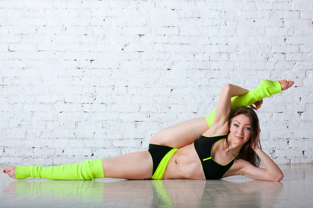 Pretty sporty strong slim and fit young woman sitting, doing split and stretching exercises, sitting on a full split. In studio, against brick wall, mirror reflection on the flloor photo