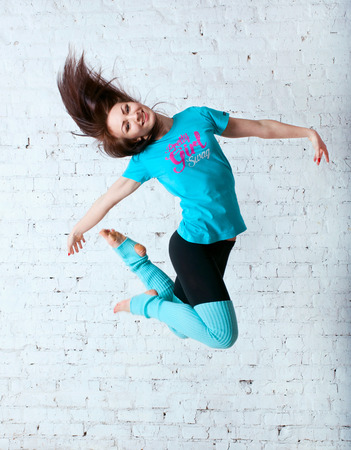 gaiters: Pretty sporty barefooted woman dancer wearing black leggings, blue t-shirt and gaiters, dancing, jumping up in the air, posing, smiling and looking happily at camera. Over a brick wall
