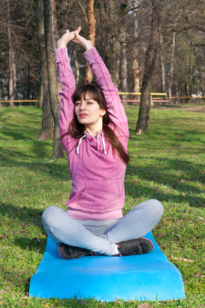 Sporty young woman doing stretchinh on a yoga mat during workout outdoors at nature. On a bright sunny day in the park photo