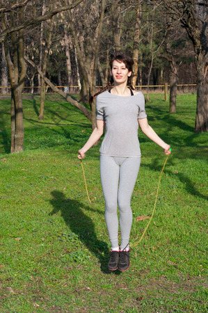 Pretty sporty fit woman doing workout outdoors, jumping with a skipping rope, having fun on a bright sunny spring day in a park Stock Photo
