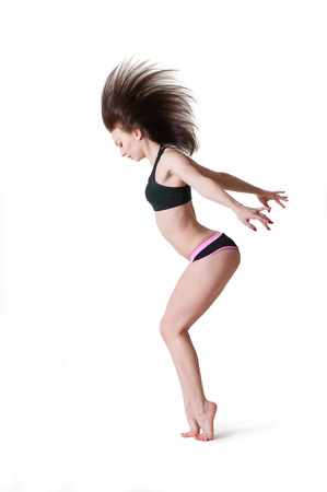 barefooted: Pretty sporty barefooted woman dancer wearing black top and black pink shorts, dancing, posing, standing on her tiptoes, hair flip up in the air. Over white background