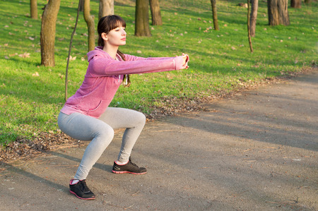 Strong sporty woman doing squat exercises outdoors on fresh air in the park on a sunny spring day. Copy space