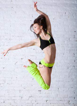 Pretty sporty barefooted woman dancer wearing black yellow concert costume, dancing, jumping up in the air, posing, smiling and looking happily aside. Over a brick wall background photo