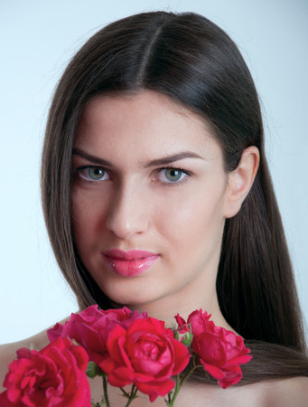 Young pretty woman model with healthy long straight brunette hair, natural makeup, tender glossy lips, gray eyes, holding twig with red roses near face, looking at camera. Grey background photo