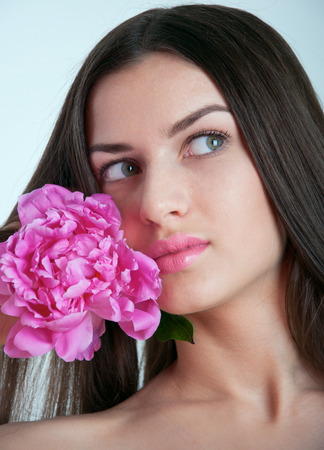 Beautiful young woman model with healthy long straight brunette hair, natural makeup, tender glossy pink lips, holding pink peony on her shoulder, smelling it, looking aside and smiling. Gray background