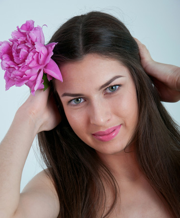 Beautiful young woman model with healthy long straight brunette hair, natural makeup, tender glossy pink lips, putting pink peony flower into her hair, looking at camera and smiling. Gray background photo