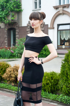 Pretty young brunette woman model wearing black top and long skirt, elegant high heels, holding her coat and bag, walking down an alley, looking aside and enjoying the day.  photo