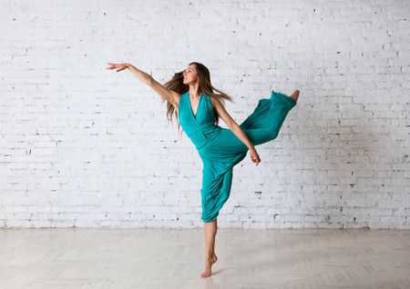 Young beautiful woman dancer doing pirouette, posing, dancing, jumping in a studio, standing on a tiptoe, her blue turquoise long dress getting into drapes, hair flyong in the air. Over brick wall background 版權商用圖片