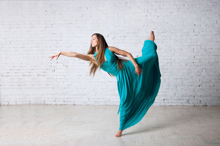 pirouette: Young beautiful woman dancer doing pirouette, posing, dancing, jumping in a studio, standing on a tiptoe, her long blue turquoise long dress getting into drapes, hair flyong in the air. In studio over brick wall background Stock Photo