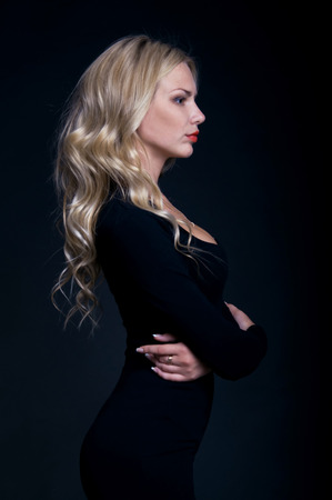 wil: Studio profile photography of an elegant posh blond woman model wil long curly locks hairstyle wearing a tight black cocktail dress and red lipstick. Over black background