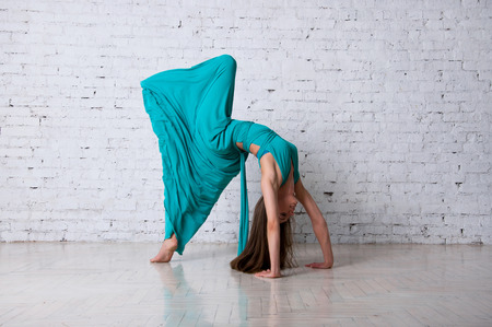 Pretty woman dancer doing pirouette, posing, dancing, jumping in a studio, standing on tiptoes, long blue turquoise long dress getting into drapes, hair flying in the air. Over brick wall background