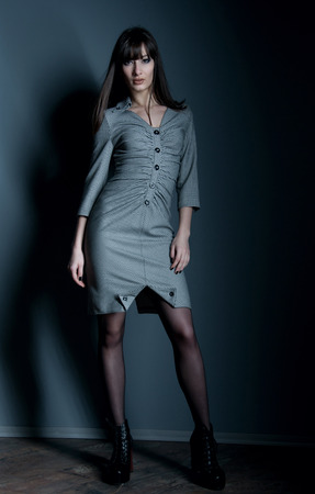 Pretty confident business woman with long straight hair wearing an elegant dress, standing, looking at camera. Over dark gray background in studio environment photo
