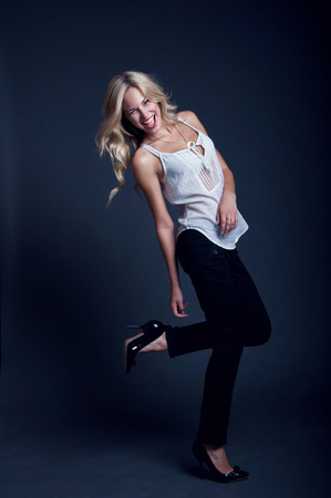 Happy laughing blond business woman wearing trousers and white shirt, having fun, dancing, jumping in studio over dark gray background