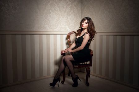 Young beautiful brunette woman wearing tight black dress and high heels, red lipstick, siting on the antique chair and posing in interior in studio, looking at camera.