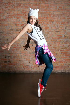Young pretty teenage dancer standig on tiptoes, posing in studio against brick wall background photo