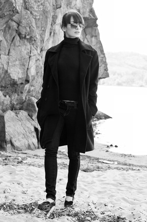Elegant beautiful brunette woman model wearing tutpleneck sweater, coat, jeans, sunglasses, walking along the beach near rocks on a bright sunny day. Autumn fashion. High key portrait photo