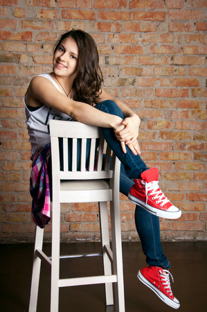 Pretty funny teenage girl wearing casual street style clothes, sitting on a bar chair, smiling, looking at camera. Against brick wall background in studio photo