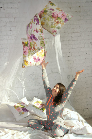 Pretty brunette teenage girl wearing pijamas, playing with pillows on a bed in the morning. Over brick wall background