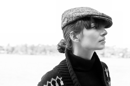Black and white profile portrait of pretty young woman wearing black turtle-neck, boyish peaked cap and sweater, looking aside. High key portrait, copy space photo