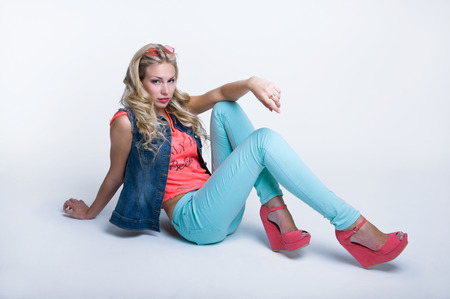 Pretty slim blond woman model with amazing long legs wearing round sunglasses on forhead, bright pink top, blue denim vest, turqouse pants and stylish platform shoes, posing, sitting on the floor, looking at camera. Over white background photo