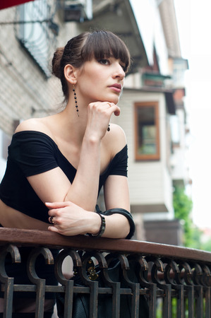 Pretty slim young brunette woman model wearing black off-the-shoulder top, elegant earrings, beautiful hairstyle, leaning over the balustrade of a balcony, looking somewhere, dreaming and enjoying the day.