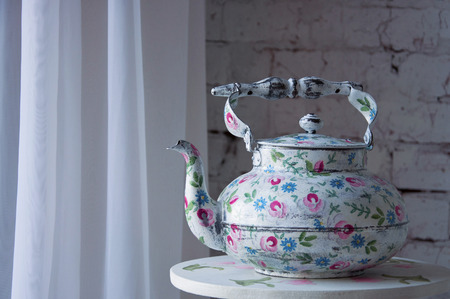Vintage white tea pot with floral pattern standing on the table photo