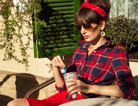 Pretty brunette woman wearing red skirt, checked shirt, band, aviator sunglasses, resting in a wickered chair in a street cafe, drinking her cold milk shake cocktail. On a hot summer day photo
