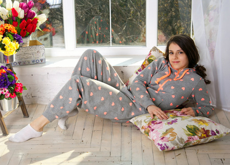 Cute funny teenage girl wearing pijamas, lying on the floor on pillows, enjoying her morning, smiling and looking at camera. Near the big french window